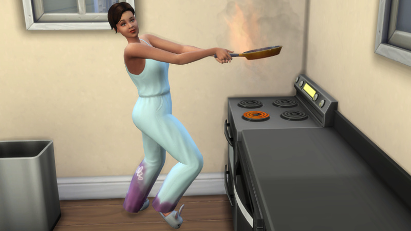 Stacey holds a frying pan which is on fire
