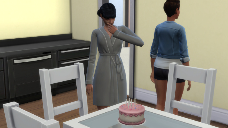 Zoe strokes her chin in front of a birthday cake