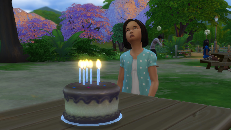 Britta stands at the birthday cake