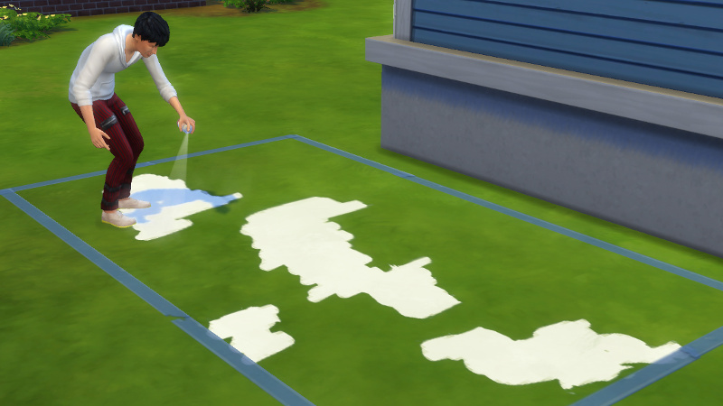 Julian paints a mural on the grass behind the house