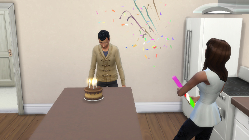 Abed peers at a birthday cake as Claire releases a confetti popper and confetti falls through the air